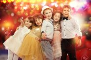 34654558-group-of-happy-kids-in-celebratory-clothes-with-colorful-lights-on-background-holidays-christmas-new