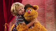 A little boy and Fozzie hugging