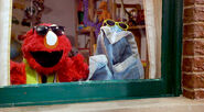 Elmo sings while playing with his blanket