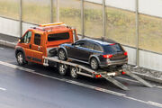 Homeguide-tow-truck-service-transporting-car-on-highway.jpg