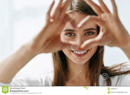 Beautiful-happy-woman-showing-love-sign-near-eyes-healthy-vision-portrait-holding-heart-shaped-hands-closeup-smiling-83939671