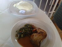 Chicken served with a side dish of nshima.