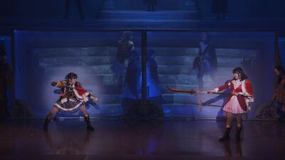 A screenshot of the first stage play picturing Maya and Kaoruko in their Revue outfits. They point their weapons at each other in preparation for their fight. Behind the wall, Claudine and Futaba watch them from the stairs.
