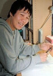 A Japanese man, smiling, wearing a grey hoodie while working at a desk.