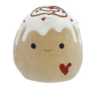 A smiling light brown cinnamon roll plushie with two hearts stitched onto her stomach. She has white icing on her head that drips down her body with a brown swirl that is loosely in the shape of a heart. There are smaller red hearts dispersed throughout the icing and swirls.