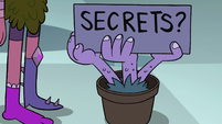 S2E1 Potted hand-plant with 'Secrets?' sign