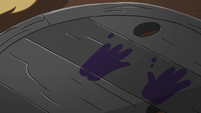 S4E30 Well cover with black handprints on it