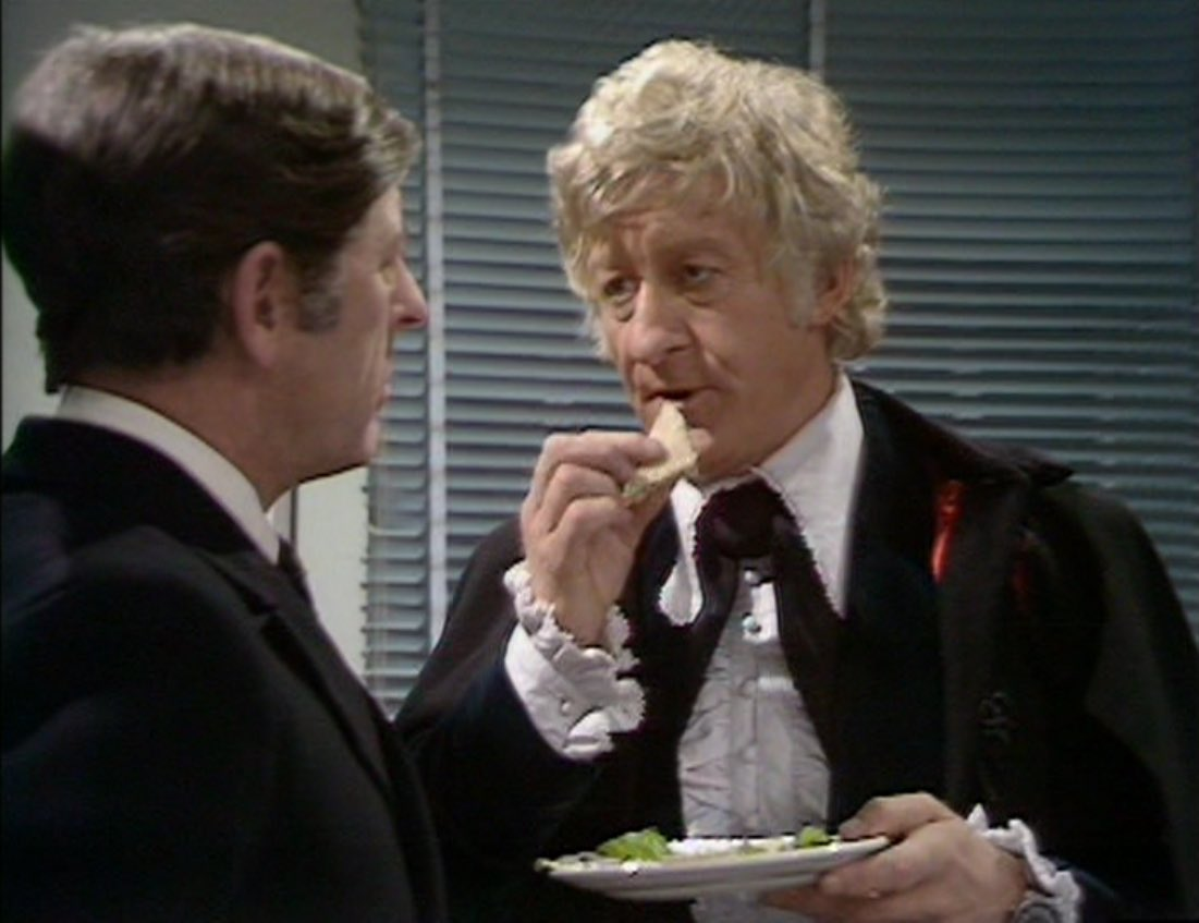 The Doctor eats sandwiches holding plate.jpg