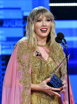Taylor Swift is looking away from the camera, smiling, and holding an award.