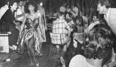 Transwoman sashaying down Bugis Street, being ogled at by tourists, circa the 1960s