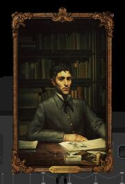 A dark haired, skinny, dapper man posed in front of a writing desk.