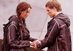 Katniss y Peeta a punto de comer la bayas.png
