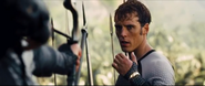 Katniss aiming her arrow at Finnick