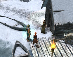 Valdis, the scholar of Kaupangr, stands in front of a hut