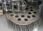 Circular broom under street sweeper