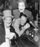 Three smiling live-action villains next to electronic equipment