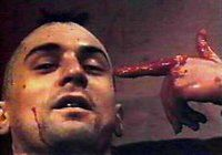 Head and right hand of a man, shot from a slightly low angle. The man, whose hair is in a Mohawk, looks down at the camera with an odd smile. A spot of blood is on his upper left cheek, and a three-inch line of blood runs from his lower left cheek to his jaw. With his blood-drenched thumb and index finger, he makes the shape of a pistol, pointed at the side of his head.