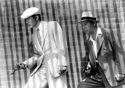Black-and-white image of two men facing the left of frame, walking in front of a brick wall. A bold series of vertically striped shadows covers the entire image. The middle-aged man to the right wears a white fedora, a medium-dark suit, and an open-collared white shirt. In front of him, to the left of the image, a younger, taller man wears a cream-toned suit, a white beret and shirt, and a light striped tie. Each man holds a pistol in his right hand.