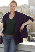 Melissa Rosenberg standing against a city background.