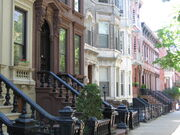 A view down a street with rowhouses in brown, white, and various shades of red.