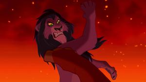 Scar knocks Simba down.