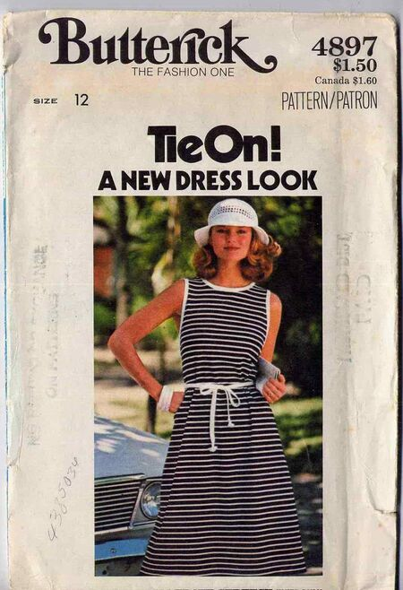 Circa 1977. Wrap dress has U neckline, cutaway armholes and purchased foldover braid finish extending into ties. Made with only two pattern pieces, no buttons, zippers, snaps or hooks.