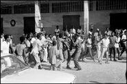 Гаитянские солдаты разоружают тонтон-макутов после того, как стало известно, что дювалс ушел с поста, 7 февраля 1986 г.