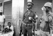 Tonton Macoute (center) with soldier; fearful female street vendor.
