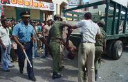 Гаитянские люди смотрят на убитого тонто-макута, 8 февраля 1986 г.