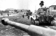 Tiger heavy tanks of Schwere Panzer-Abteilung 503 advancing through a Soviet village, Kursk 1943