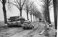 Abandoned Bergepanzer III near the Rhine sector as elements of the US 9th Army pass by, February 1945