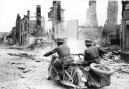 German motorcycle driving through ruined French town, France 1940